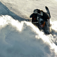 A guy on a black sled spinning on a sidehill.