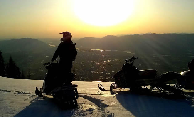A sledder is silhouetted against the setting sun looking over an amazing panorama of the town below.