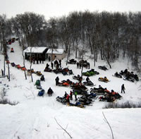 A large group of sleds gather around a cabin, seen from above.