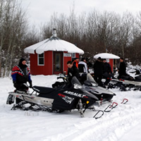 A group of sledders gather around a short, red, round building surrounded by bush.