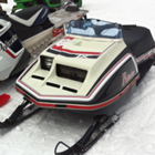 A vintage black, white and red Polaris snowmobile is parked next to a new black, white and red polaris snowmobile.