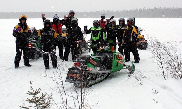 A group stand in a snowy field around a green snowmobile.