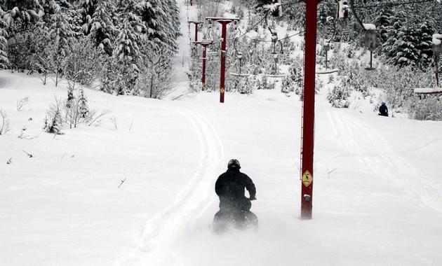 A sledder rides down the powder alongside a defunct ski lift.
