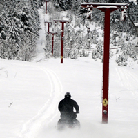 A sledder rides down the powder alongside a defunct ski lift.