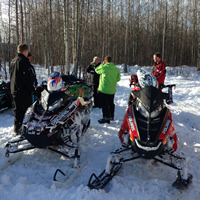 A group of riders pause with their sleds in a cabin next to forest.