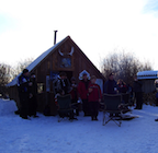 Snowmobiling warm-up shelter with a group of sledders gathered outside it.