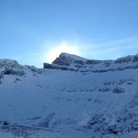 A photo of the sun going behind a snow filled mountian bowl in the Crowsnest Pass.