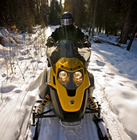 a solo snowmobiler on a forested trail