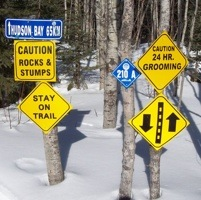 Numerous signs posted on a trail.