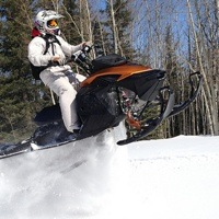 Brett Smyl taking a jump on his snowmobile.