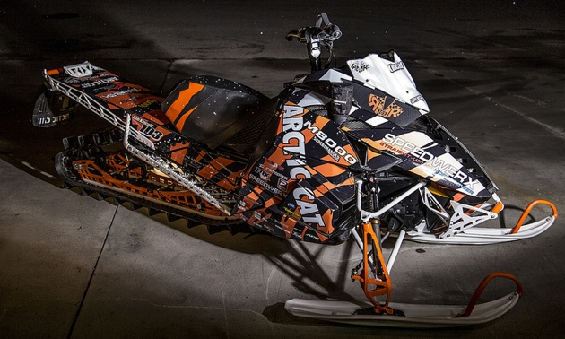 Brett Smyl taking a jump on his snowmobile.