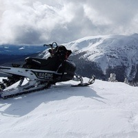 A snowmobile overlooking the Telkwa Range.