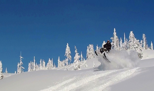A snowmobiler getting some air on a perfectly clear day.