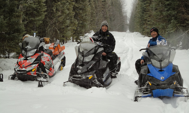 Three snowmobiles and two riders on a snowy trail among trees