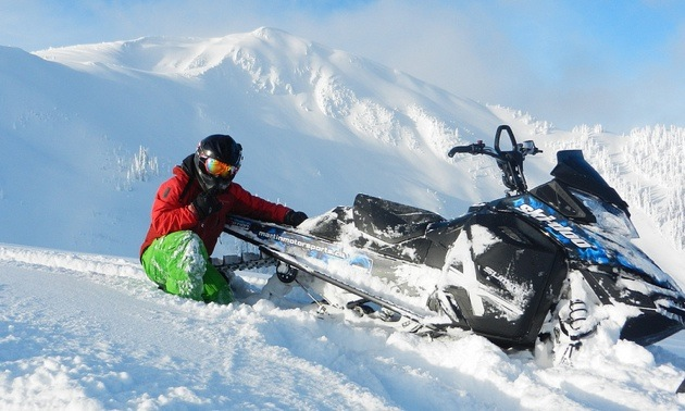 Curtis Pawliuk sitting next to his sled, enjoying the blue sky and deep powder in Valemount BC.