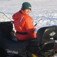 A youth enjoying ice fishing while sitting on his snowmobile.