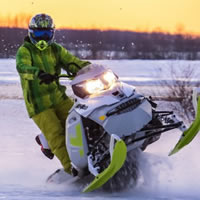 A rider in a green snowmobile suit on a green and white snowmobile.