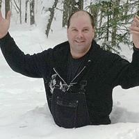 Ron Fetzko stands smiling waist-deep in snow