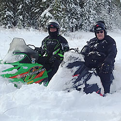 Two men sit on snowmobiles in the deep snow.