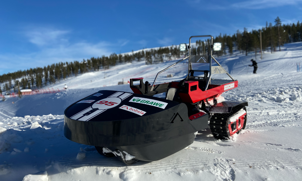 A black Bobsla electric snowmobile is parked on snow.