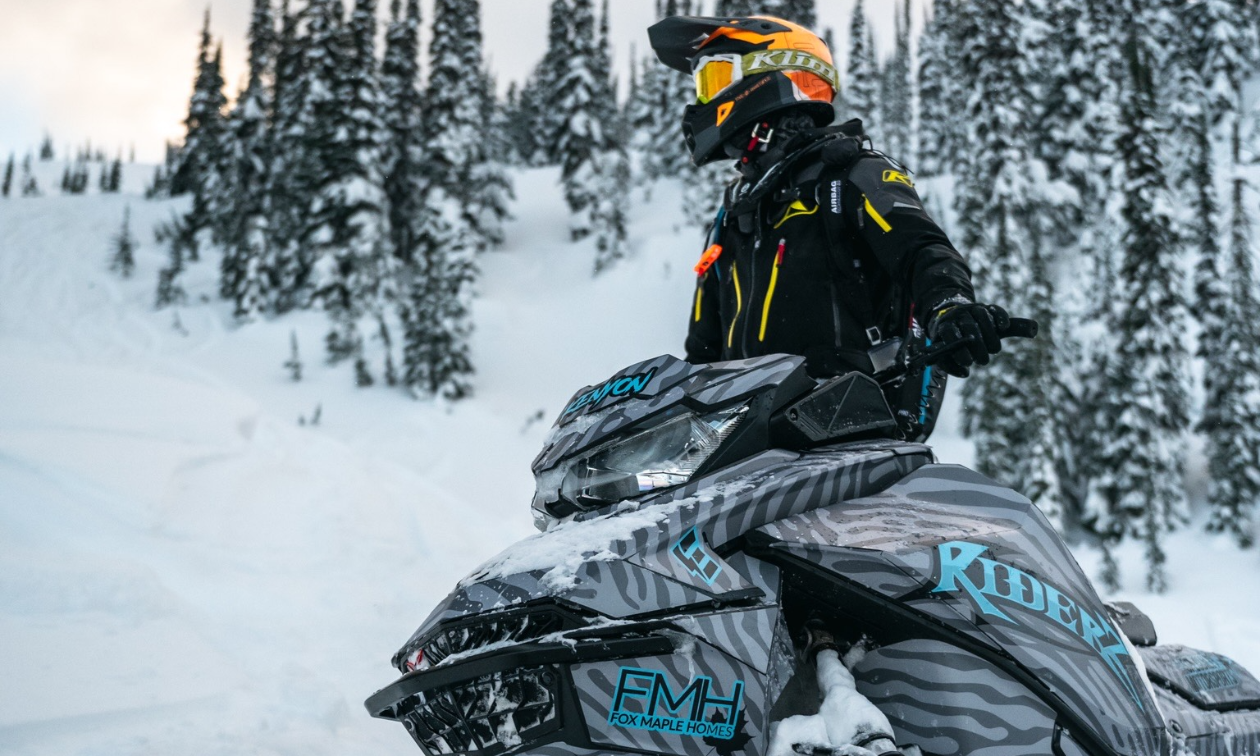 Mason Kenyon sits on his black and blue snowmobile in the mountains.