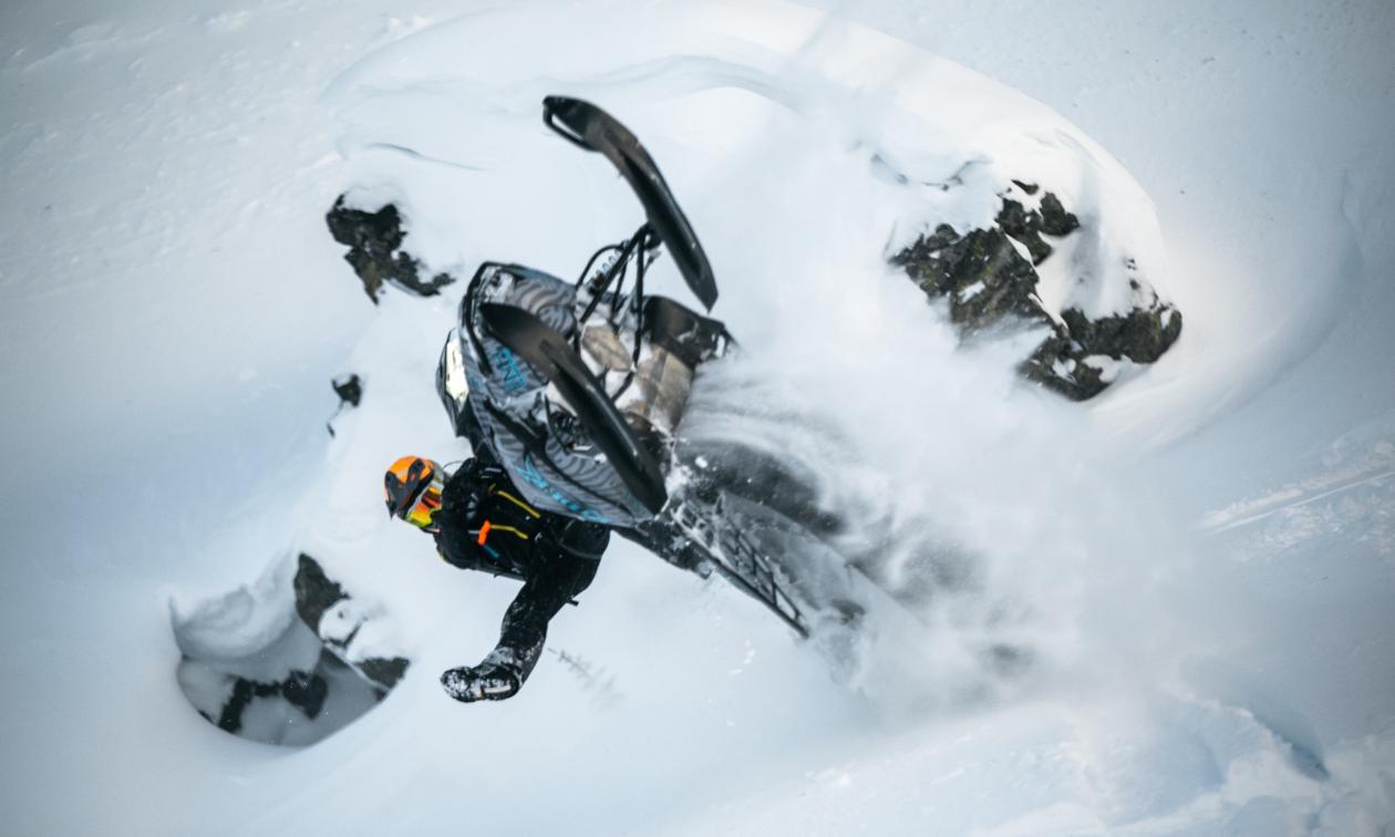 Mason Kenyon gets air on his blue and black snowmobile.