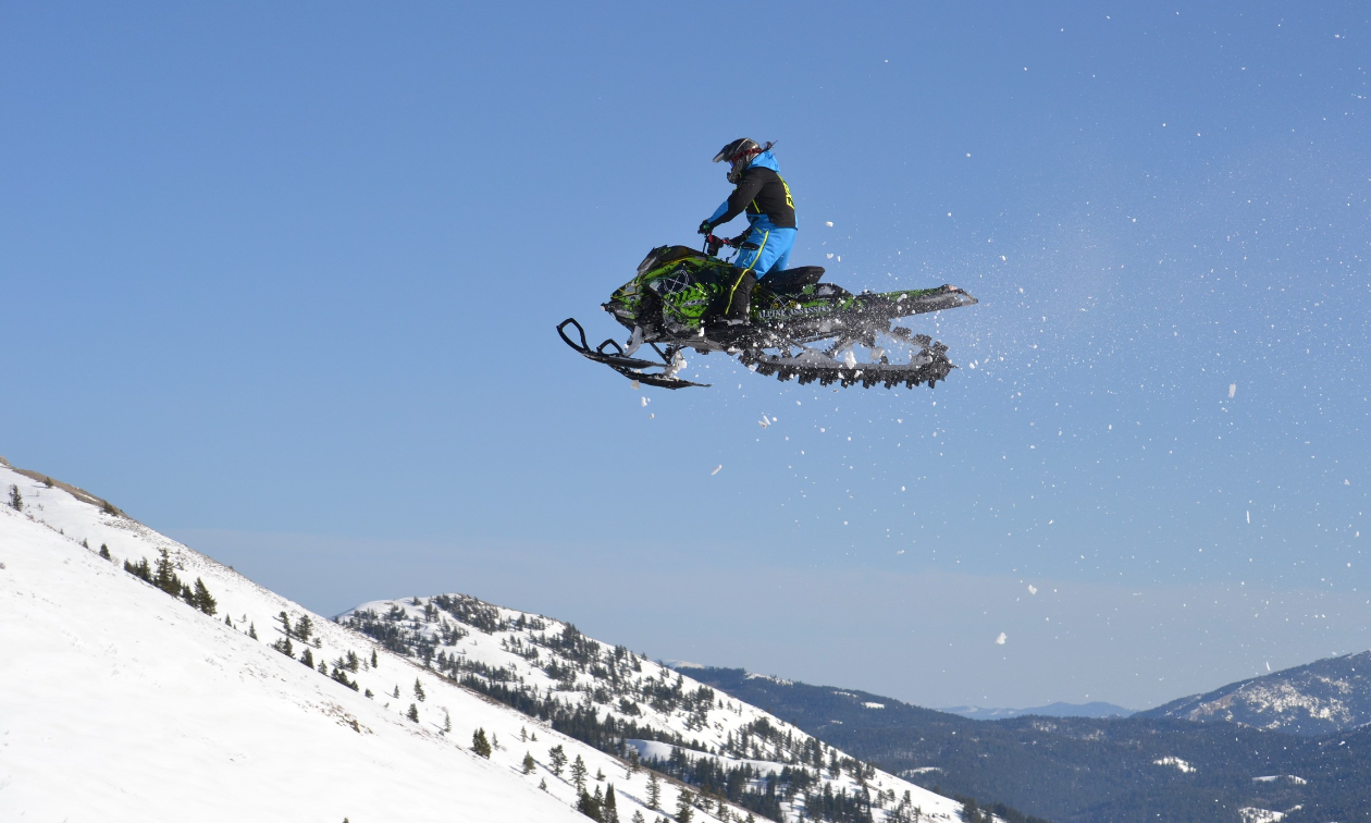 Alonzo Coby flies through the air in the mountains on a snowmobile.