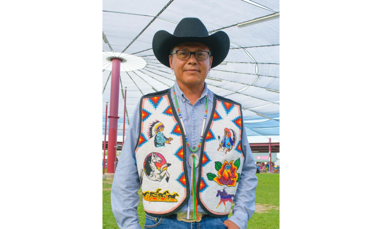 Alonzo Coby wears a cowboy hat and a colourful vest.