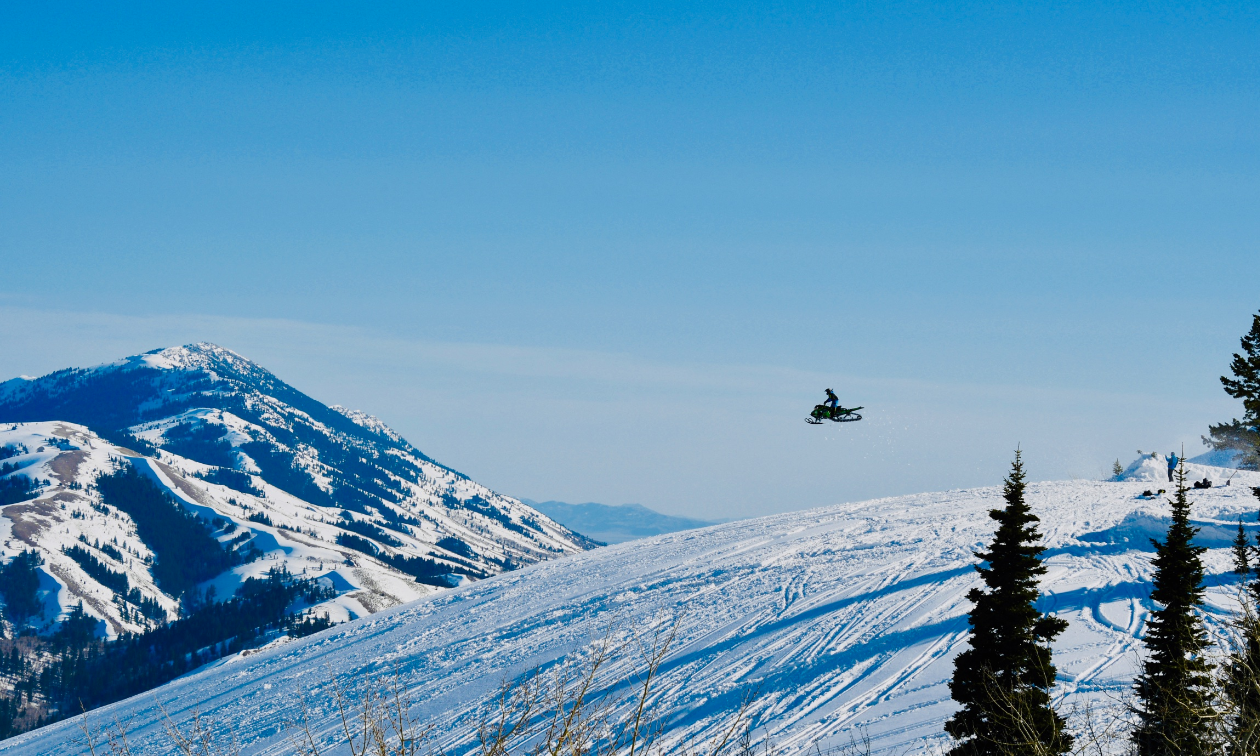 A wide shot on a mountain with Alonzo Coby flying through the air on his snowmobile.