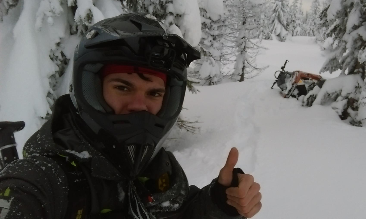 Andrew McKenzie wears a black jacket and helmet, giving a thumbs up in a snowy forest.