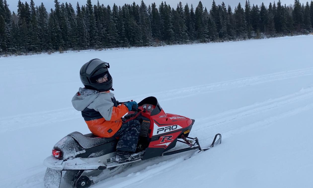 Audun Klath's son rides a small snowmobile on a prairie field.