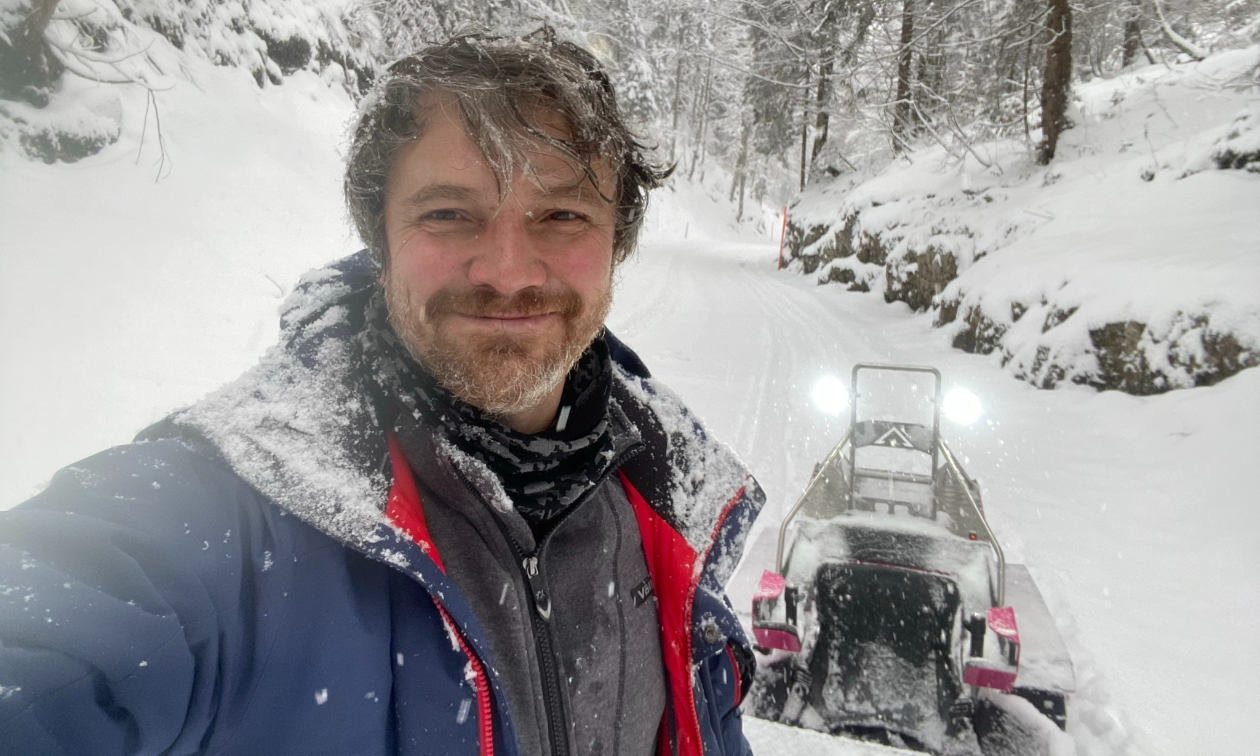 Sergey Ignatyev smiles amidst falling snow in a big blue jacket in front of his parked Bobsla electric snowmobile.