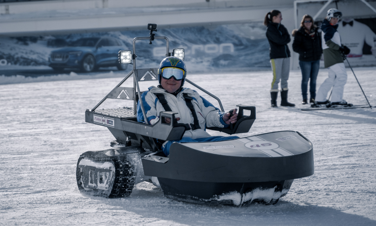 A man rides inside a Bobsla electric snowmobile.