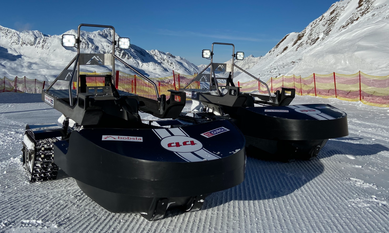 Two black Bobsla electric snowmobiles are parked next to each other on the snow.