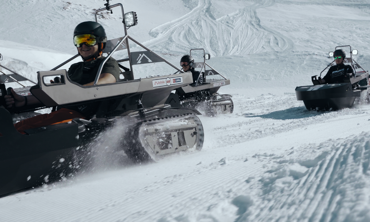 Three snowmobilers ride Bobsla electric snowmobiles on a race course.