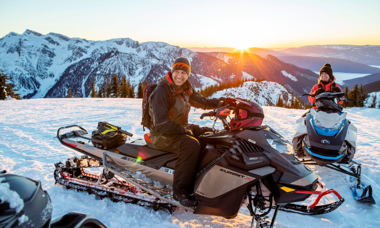 Carl Kuster sits on a 2022 Ski-Doo Summit snowmobile on top of a snowy mountain.