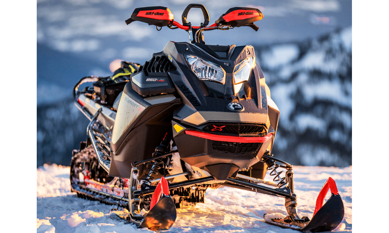 A 2022 Ski-Doo Summit snowmobile on top of a snowy mountain.
