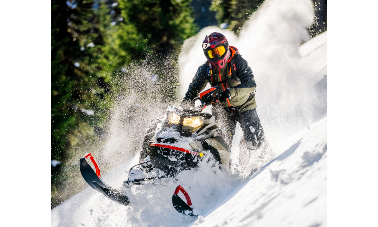Carl Kuster rides a 2022 Ski-Doo Summit snowmobile on top of a snowy mountain.