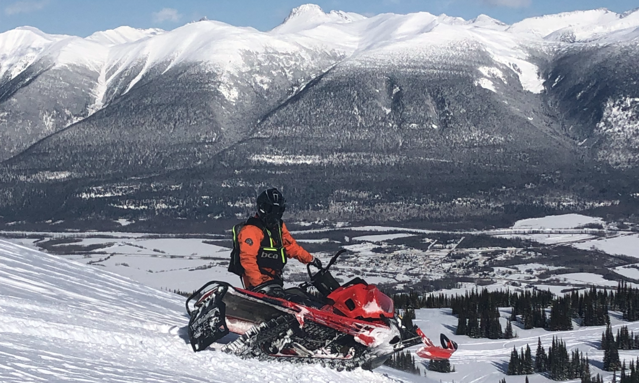 Colton Taphorn sits on a snowmobile in the mountains in McBride, B.C.