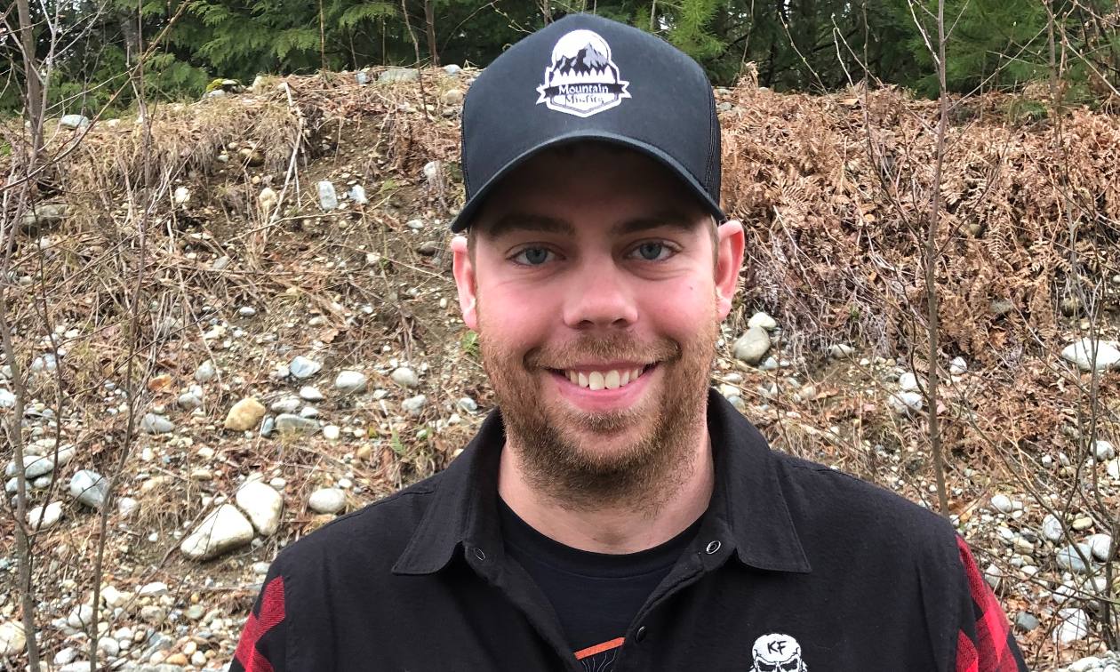 Colton Taphorn smiles, wearing a hat and a red and black long-sleeve shirt.
