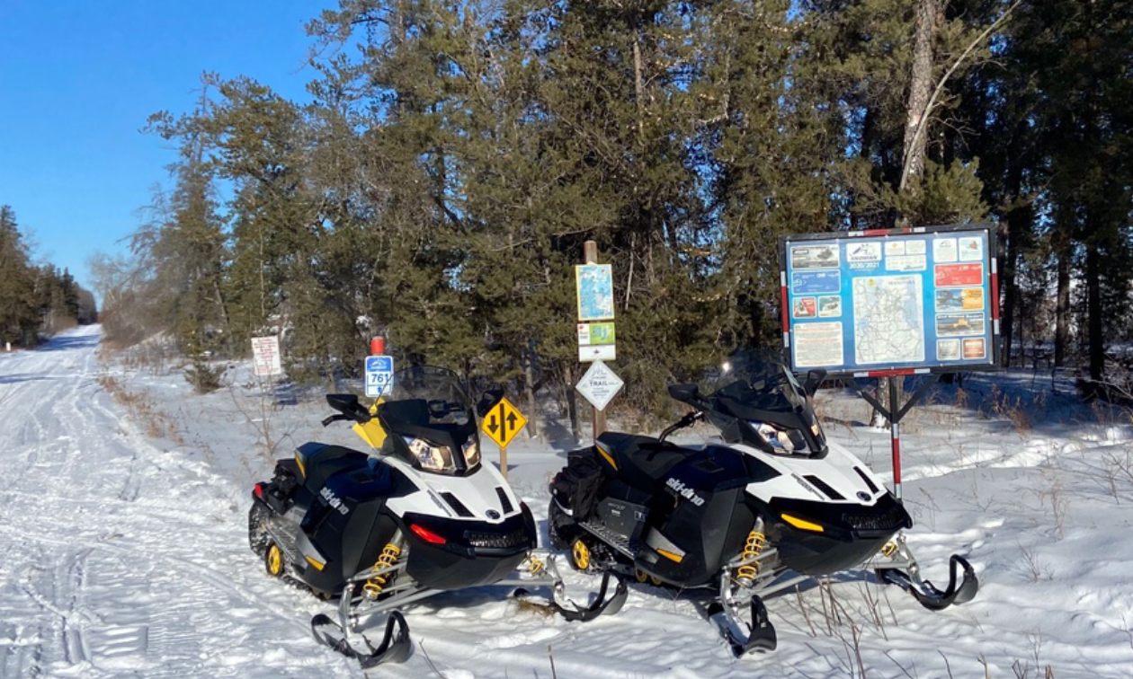 Two snowmobiles are parked in front of road signage next to a groomed trail.