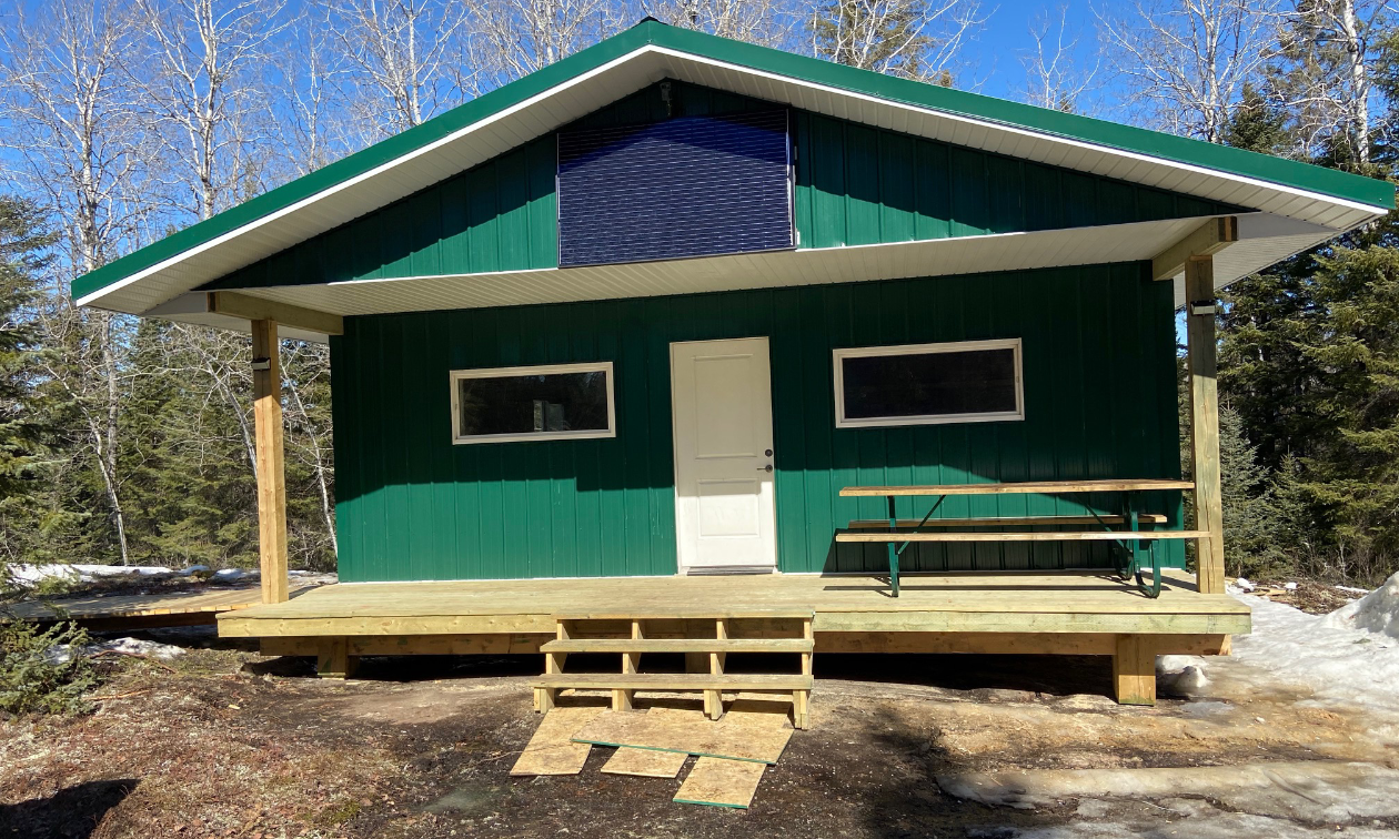 The King's warm-up shelter in Lac du Bonnet, Manitoba, is green and has metal on the outside as well as a solar panel.