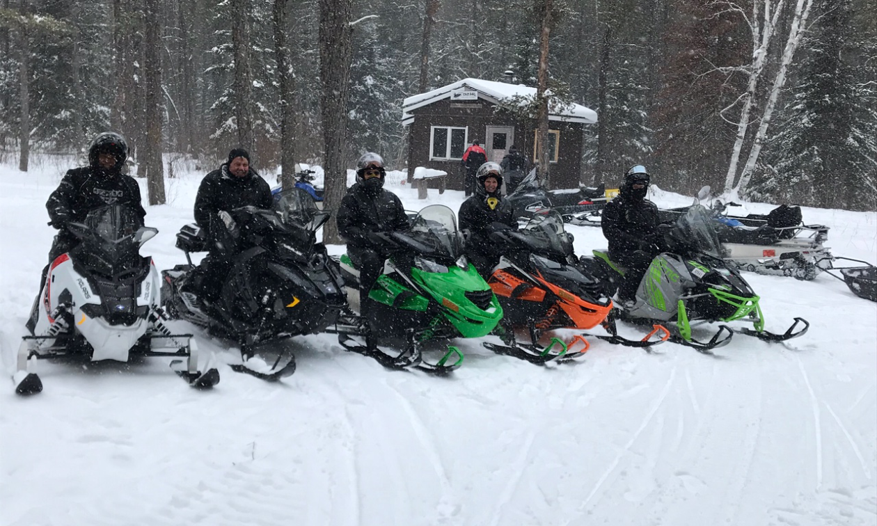 Five snowmobilers pose for a photo in front of a warm-up shelter as snow falls.