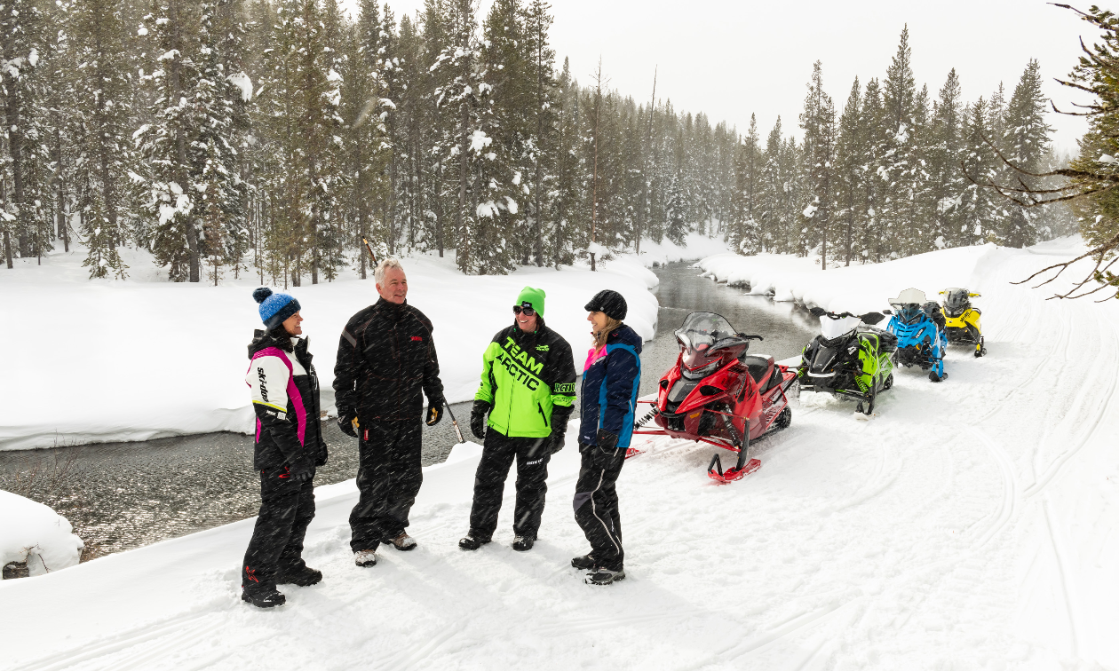 Four people visit while their snowmobiles are parked behind them next to a stream in snowy winter.