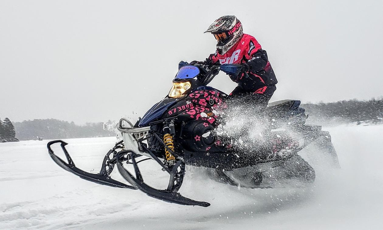 Jessica Rainville rides a black and pink 2007 Yamaha Phazer FX snowmobile.