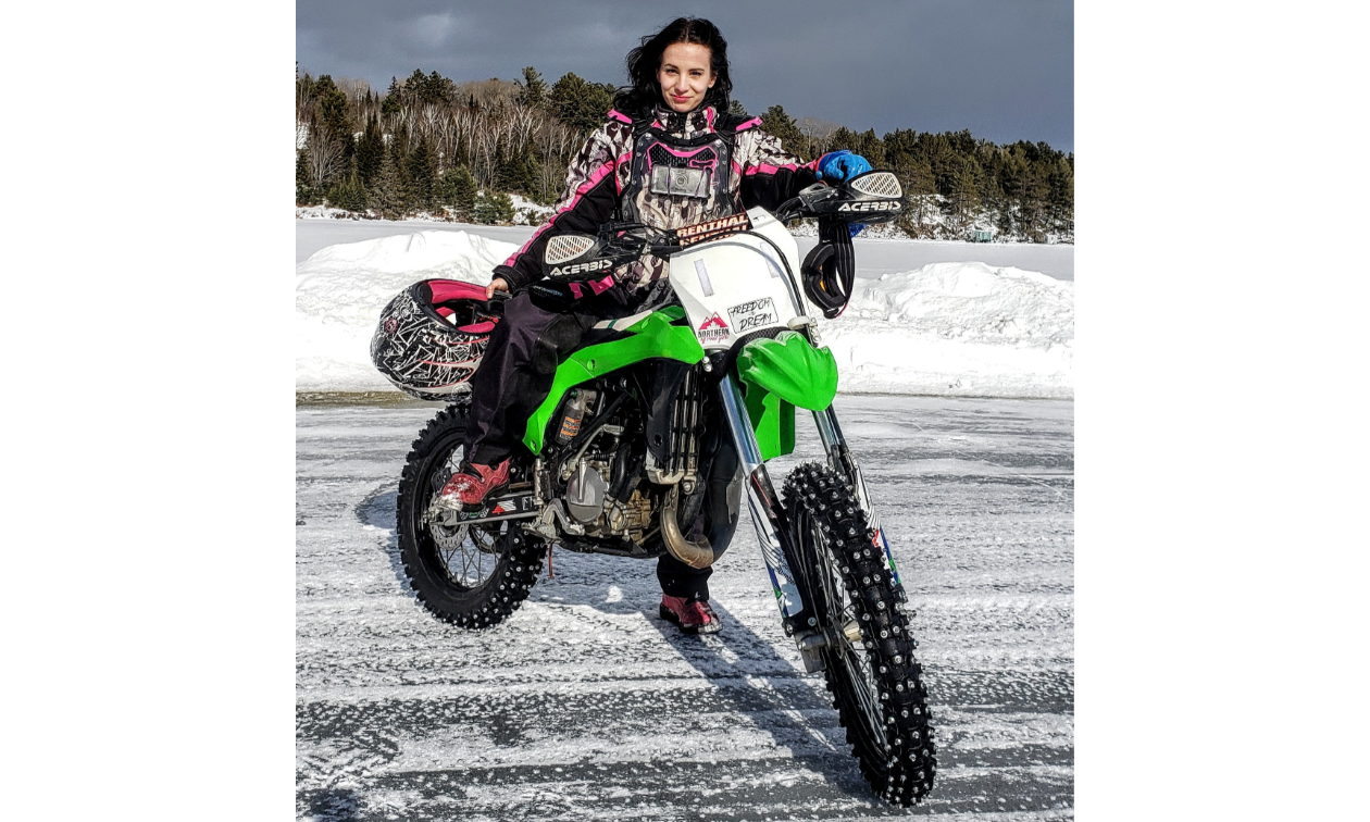 Jessica Rainville poses on a green dirt bike on ice.