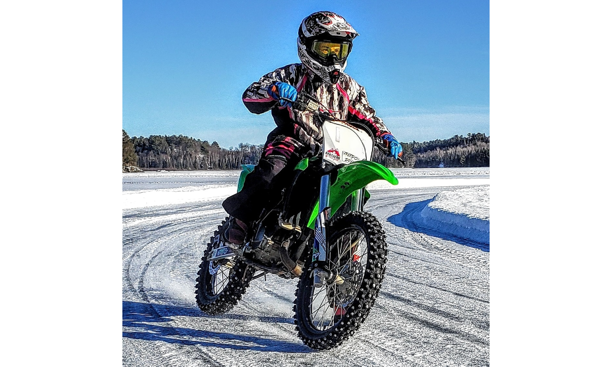 Jessica Rainville rides a green dirt bike on an icy track.