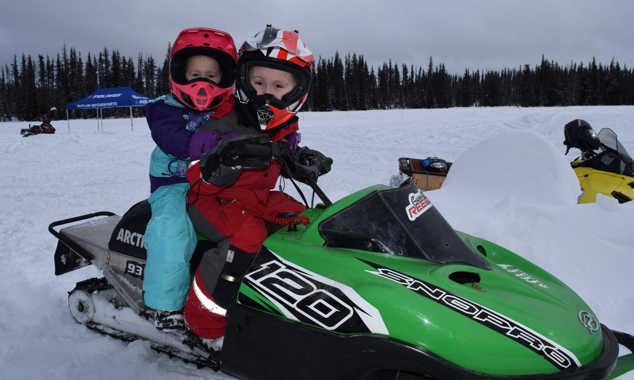 Two children ride a green snowmobile.