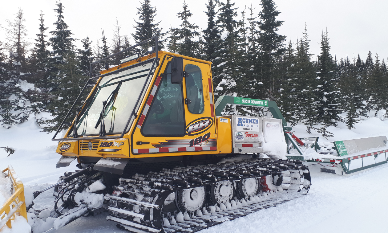 A large yellow snowmobile groomer pulls a drag behind it while clearing a trail.