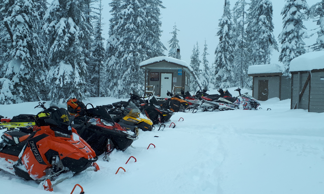 A row of snowmobiles lines the snow in front of several small warm-up shelters in Kamloops.